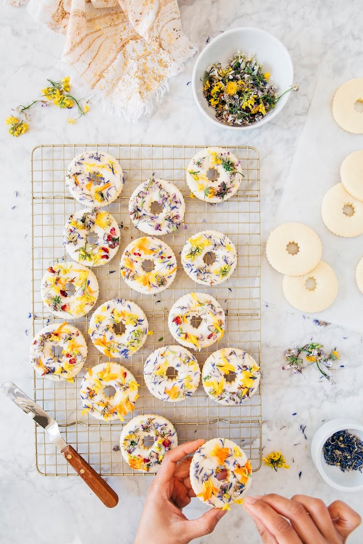 hands decorating spring flower sugar cookies