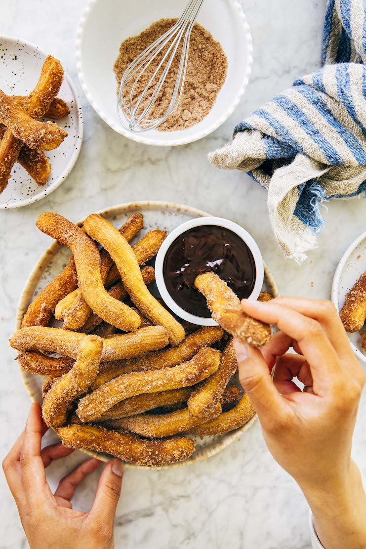 hands dipping air fryer churros into chocolate sauce