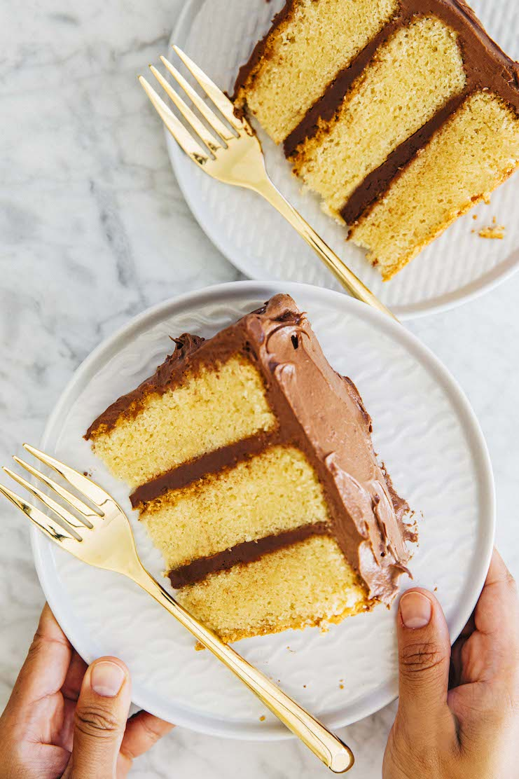 hands holding slice of yellow cake with chocolate frosting