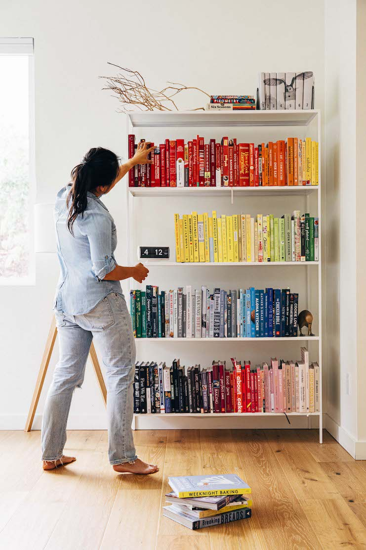 michelle browsing her cookbook collection in the Room&Board Slim Bookcase